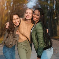 Trio pretty multiethnic cheerful teen girls posing in public park